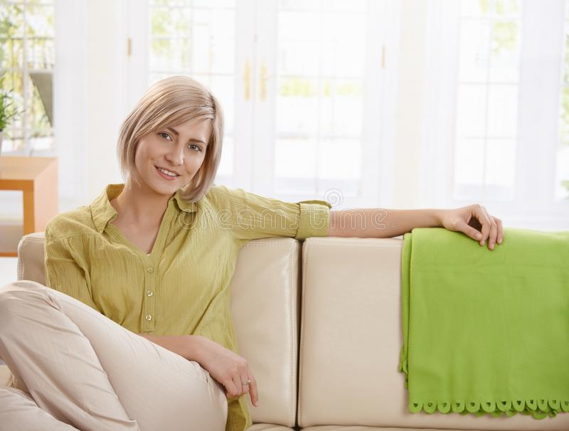 Woman sitting on sofa at home. Portrait of young blonde woman sitting on sofa at home, looking at camera smiling stock image