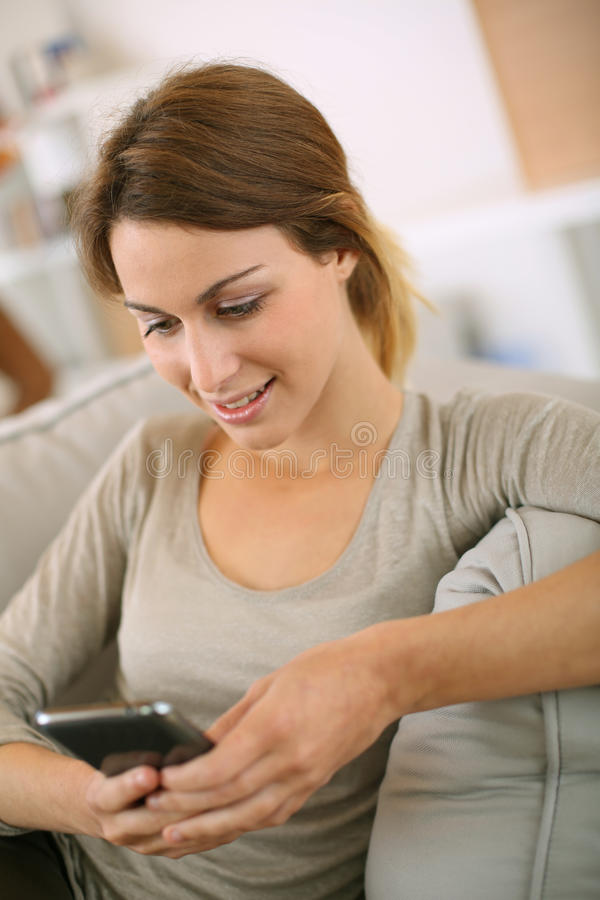 Woman sitting in sofa sending s message with smartphone royalty free stock photo