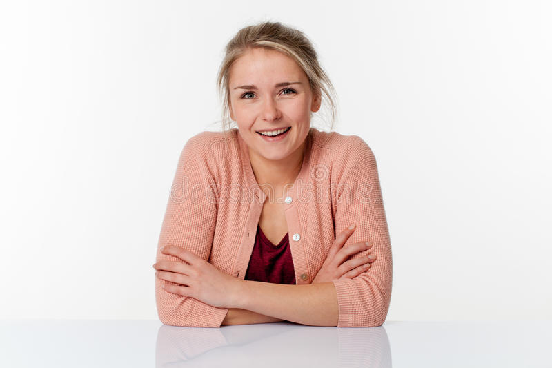 Woman sitting in sparse office expressing wellbeing at work. Serene smile - thrilled young blond woman sitting in a sparse office expressing her wellbeing at stock images