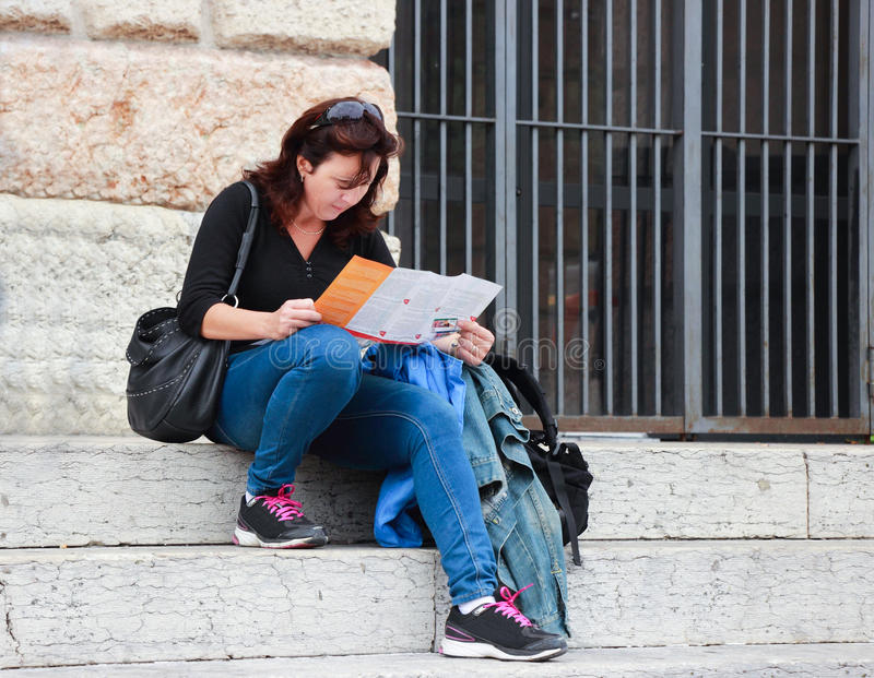 Woman sitting on the stairs and sees the map royalty free stock image