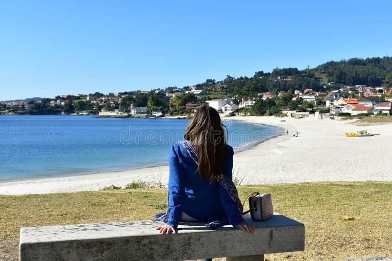 Woman sitting on a stone bench in a beach promenade. Long hair, blue clothes. Bright sand, turquoise water. Sunny. Galicia, Spain. royalty free stock photos