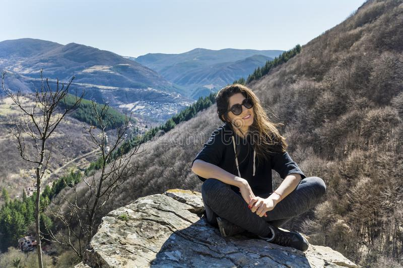 Woman Sitting on a Stone in a High Mountain. Happy woman relaxing in a high mountain royalty free stock images