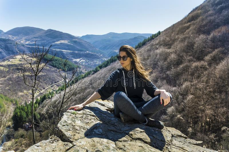 Woman Sitting on a Stone in a High Mountain. Happy woman relaxing in a high mountain royalty free stock photos