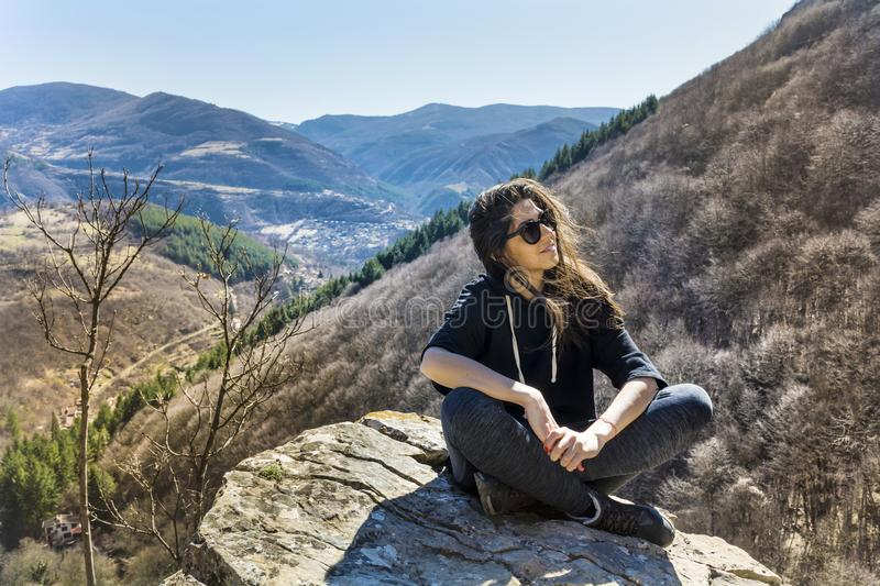 Woman Sitting on a Stone in a High Mountain. Happy woman relaxing in a high mountain stock photos