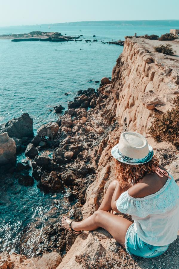Woman Sitting in Stone Near Body of Water royalty free stock images