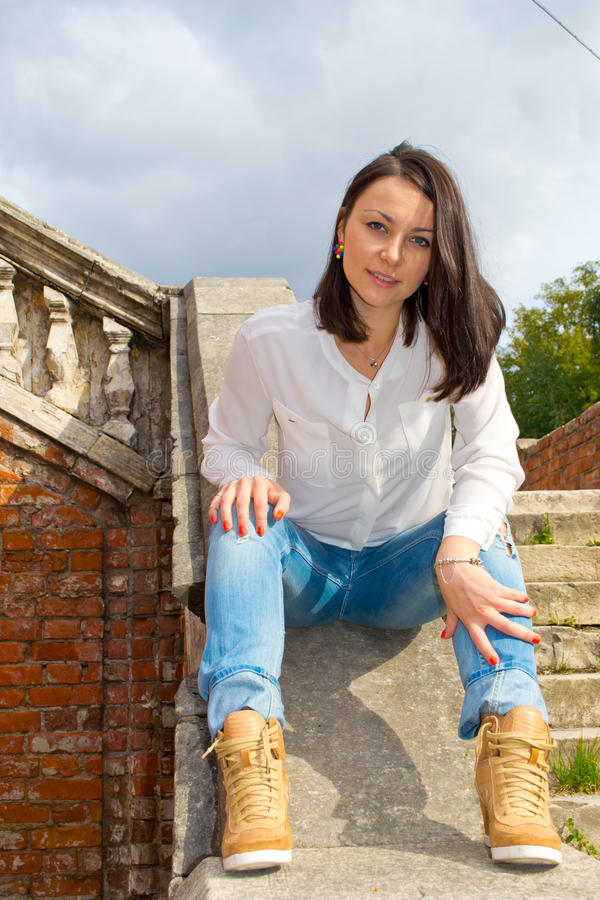 Woman sitting on stone staircase railing. Girl in a white blouse sits on a stone staircase railing of the old building stock photo
