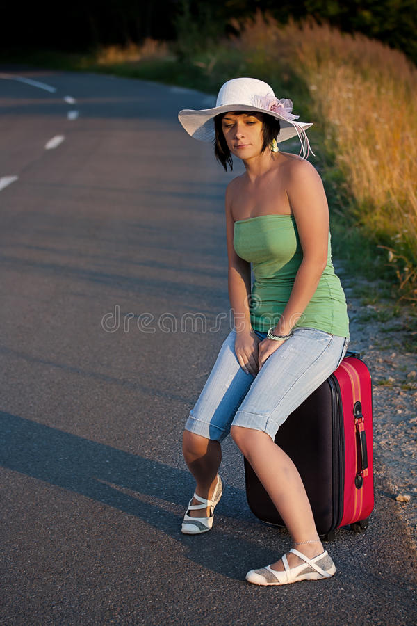 Woman sitting on a suitcase royalty free stock photography