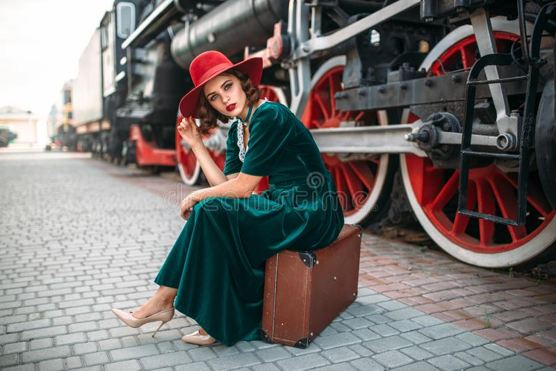 Woman sitting on suitcase against steam train stock photos