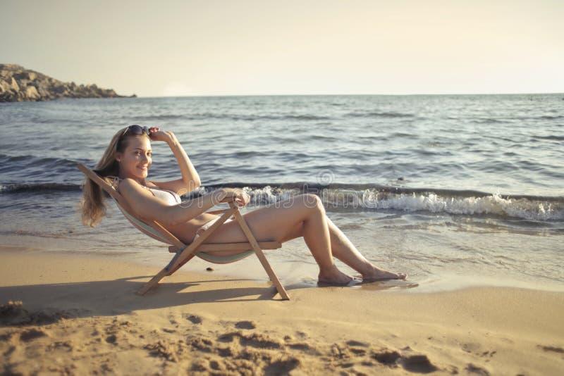 Woman Sitting on Sun Chair Beside Seashore at Daylight Photography stock photos