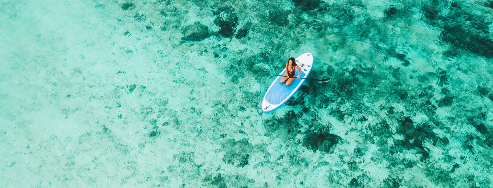 Woman sitting on sup board and enjoying coral reef royalty free stock photography