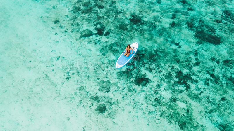 Woman sitting on sup board and enjoying coral reef. Woman sitting on sup board and enjoying turquoise transparent water and coral reef. Tropical travel royalty free stock image