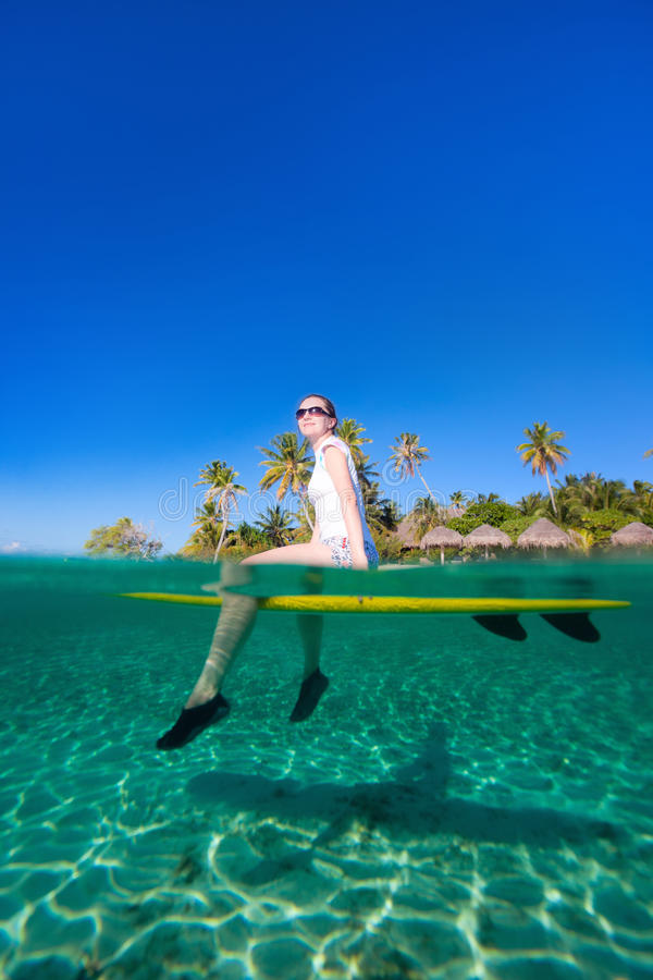 Woman sitting on a surfboard at ocean. In front of tropical island stock images