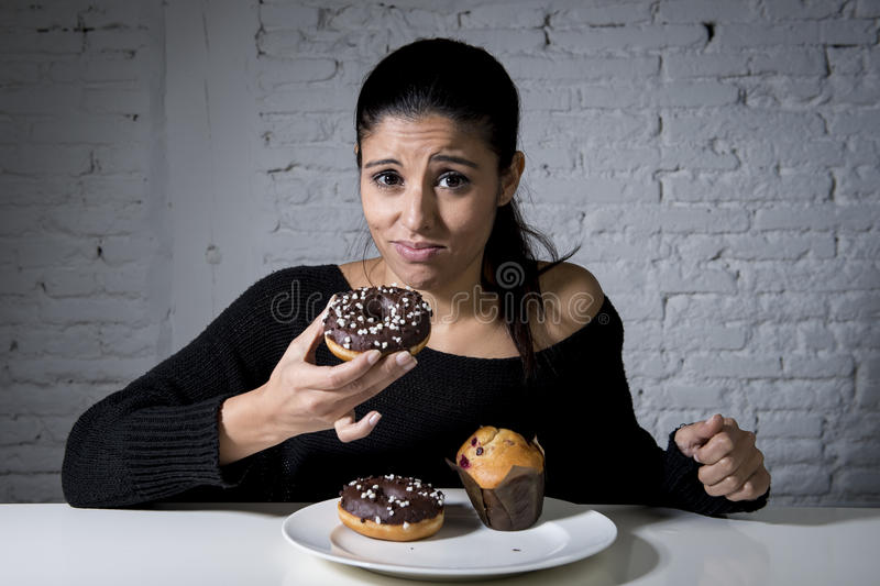 Woman sitting at table feeling guilty forgetting diet eating dish full of junk sugary unhealthy food stock photo