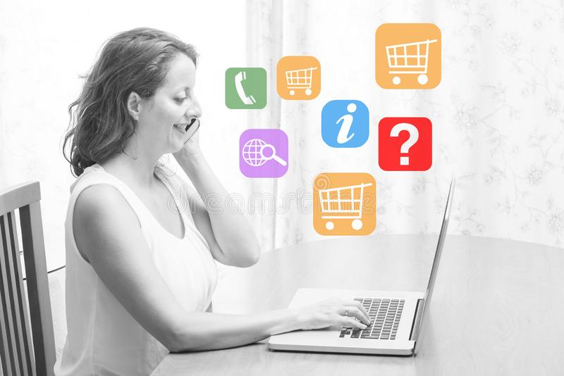 Woman sitting at the table in front of a laptop and talking on the phone. Looking for information and shopping online. Photograph illustrating the concepts of royalty free stock photos