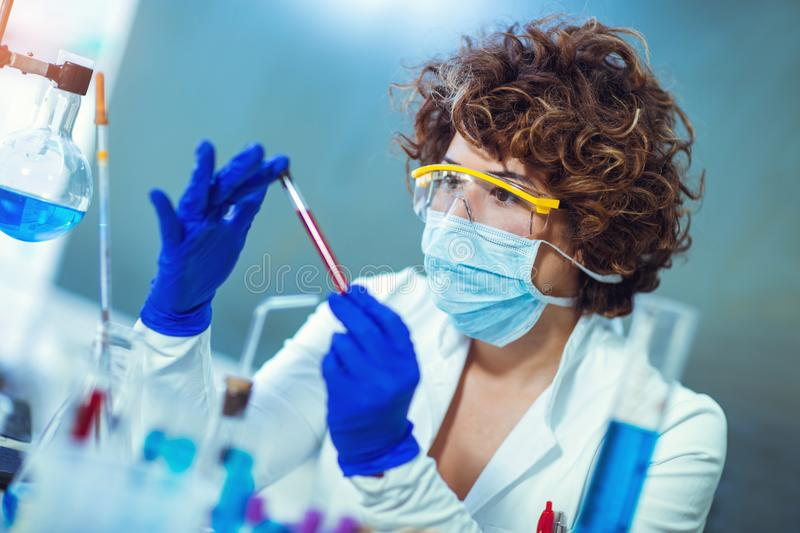 Woman in lab holding blood test tube. Woman is sitting at table in lab and holding blood test tube stock photos