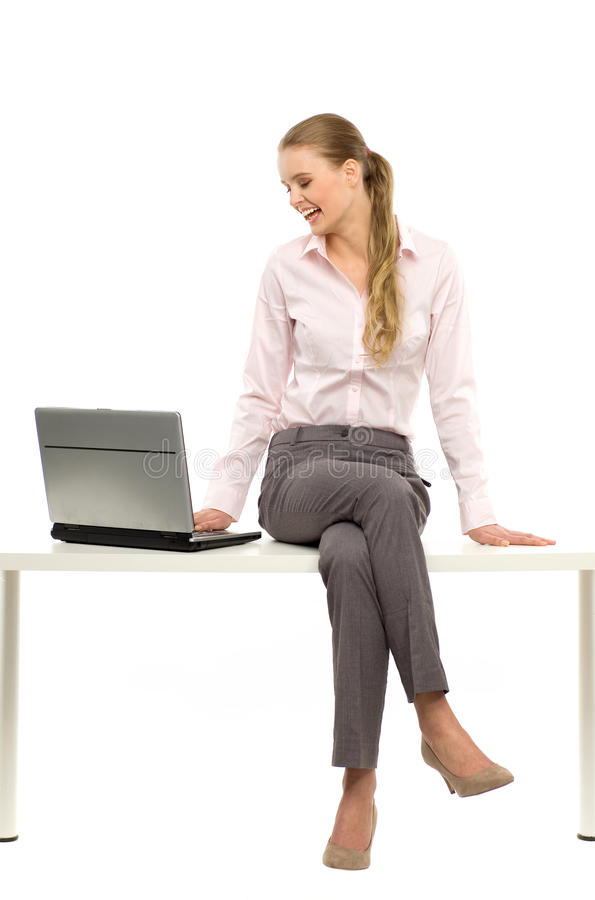 Woman sitting on table with laptop royalty free stock photos