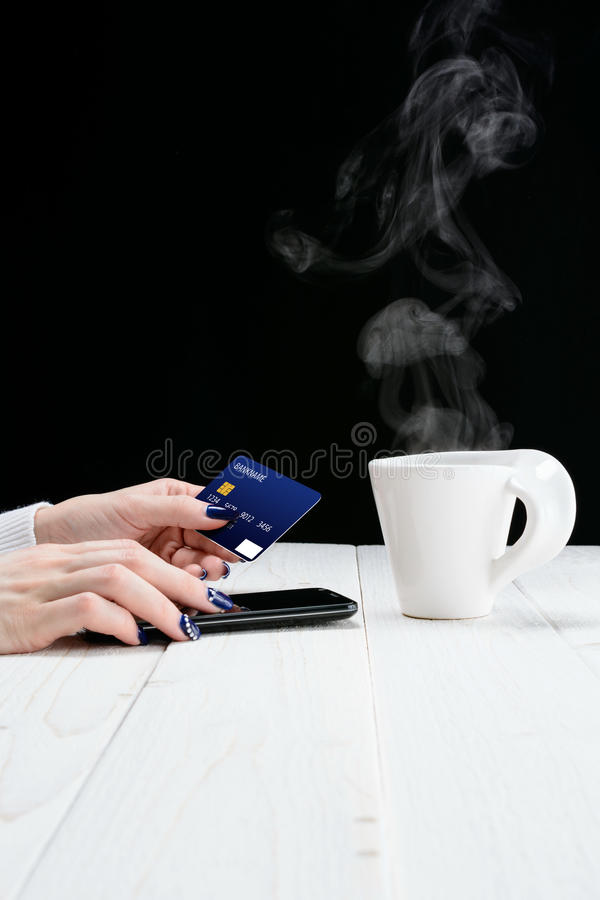 Woman sitting at table and pays the purchase through smartphone royalty free stock photo