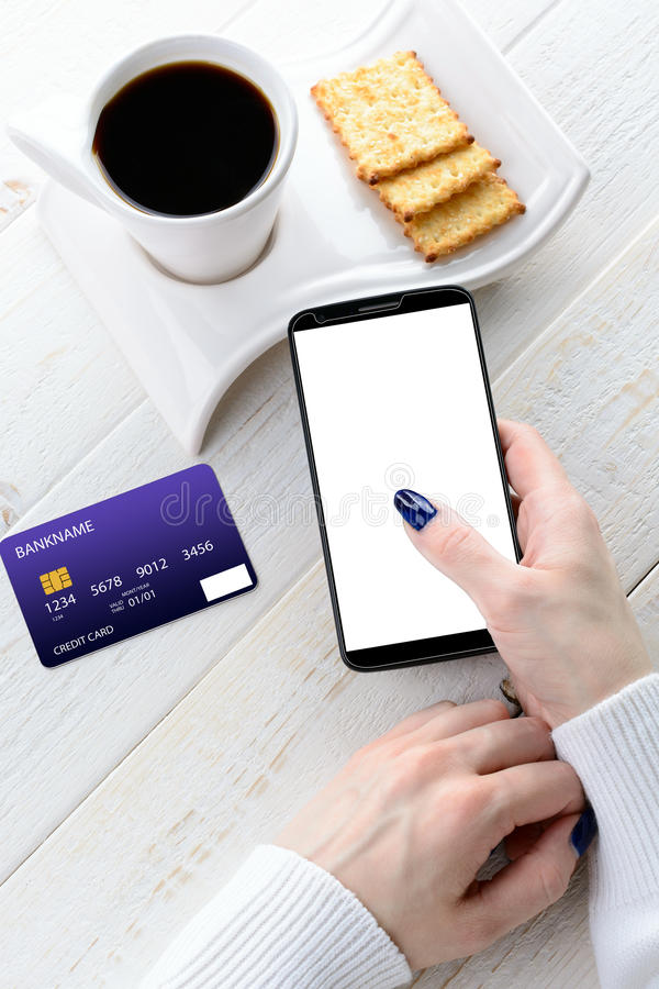 Woman sitting at table and pays the purchase through smartphone royalty free stock photography