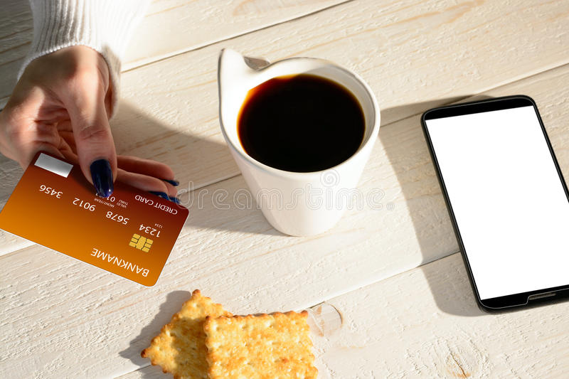 Woman sitting at table and pays the purchase through smartphone stock photos