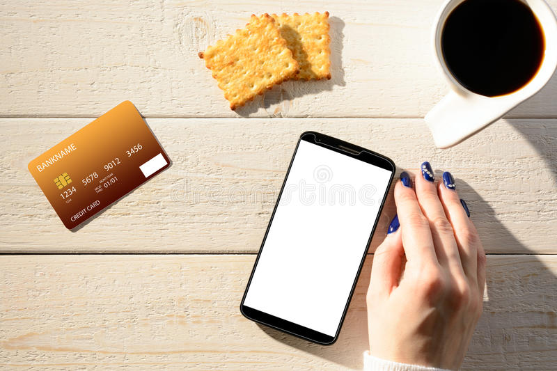 Woman sitting at table and pays the purchase through smartphone royalty free stock photos