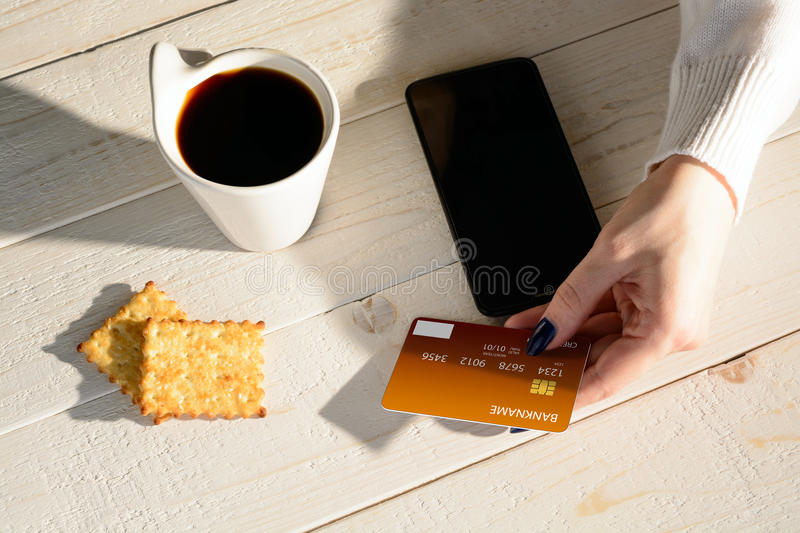Woman sitting at table and pays the purchase through smartphone stock photography