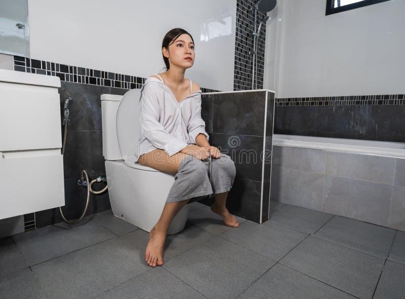 Woman sitting on a toilet stock photo