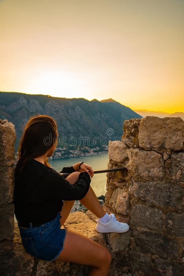 Woman sitting on top of hill on sunset with beautiful view of kotor stock photos