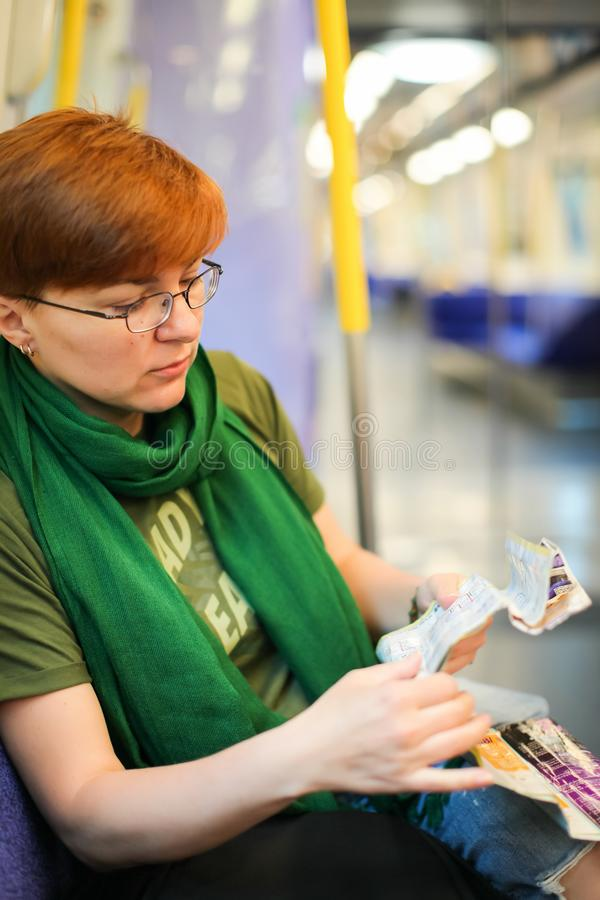 Woman sitting in train and studying route map. Caucasian tourist stock photos
