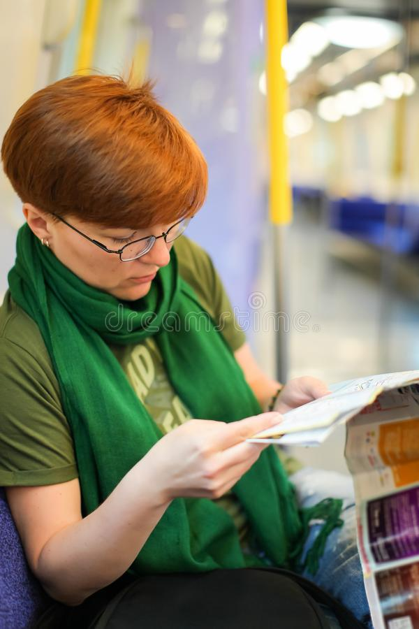Woman sitting in train and studying route map. Caucasian tourist royalty free stock photography