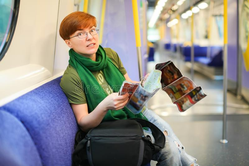 Woman sitting in train and studying route map. Caucasian tourist stock photography