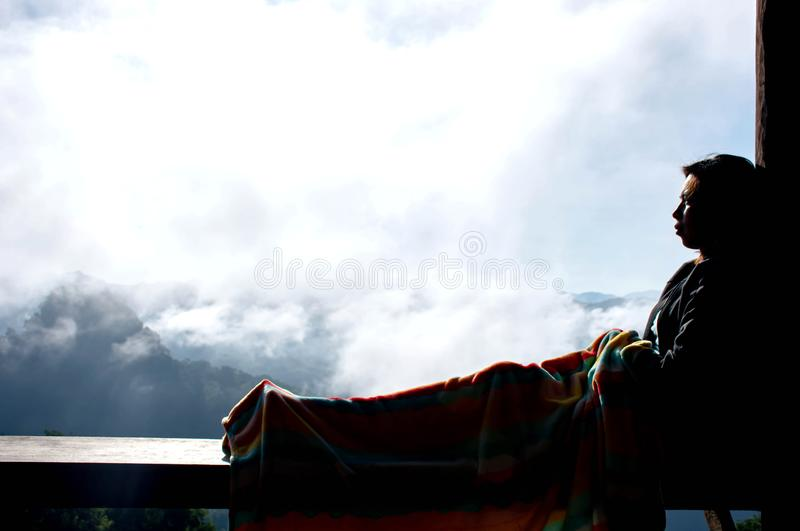 Woman sitting under a blanket and leaning pole Background fog and the mountain stock photography