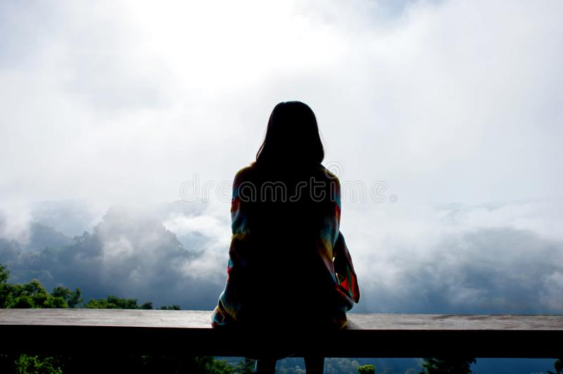 Woman sitting under a blanket and leaning pole Background fog and the mountain stock images