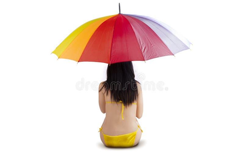 Woman sitting under colorful umbrella stock photo