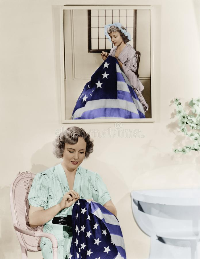 Woman sitting under the portrait of Betsy Ross sewing the American flag stock photo
