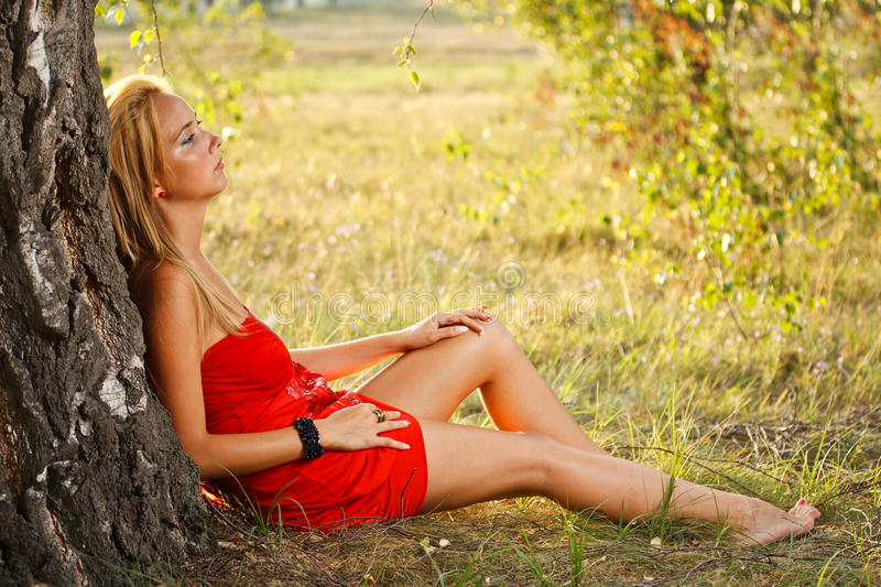 Woman Sitting Under Tree In Park Stock Images