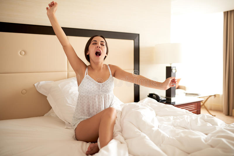 Woman sitting up in bed yawning stock image image 54364863 for Beds that sit up
