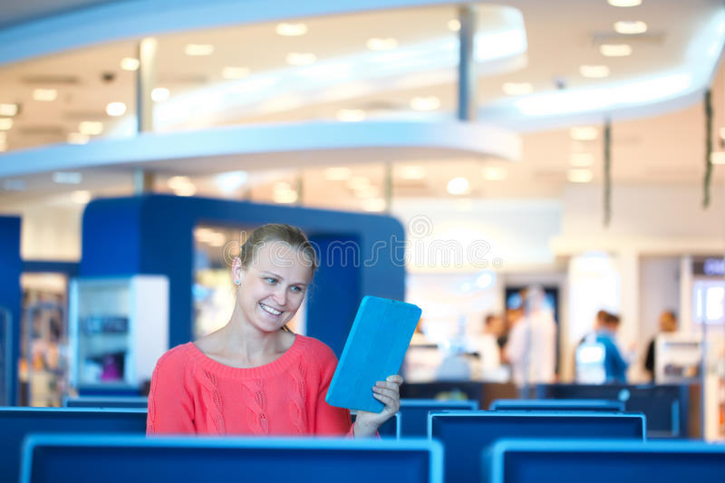 Woman sitting in a waiting room reading tablet stock image