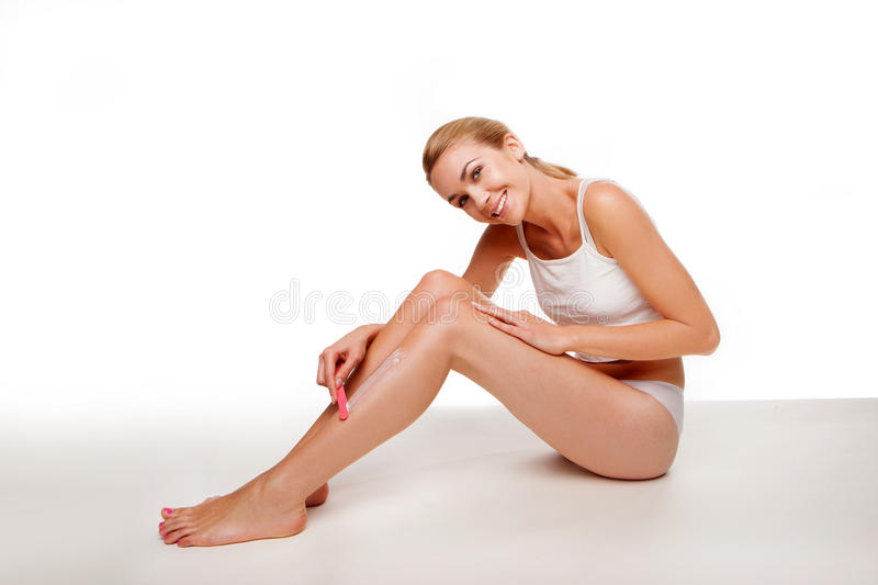 Woman sitting waxing her legs royalty free stock photo