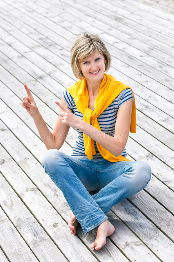 Woman sitting on the weathered wooden floor stock photography