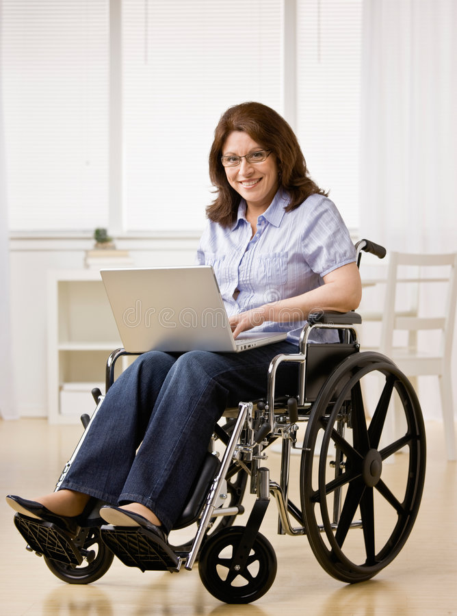 Woman Sitting In Wheel Chair Typing On Laptop Royalty Free Stock Images