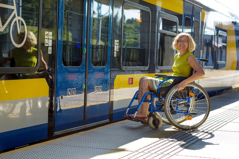 Woman sitting on wheelchair on a platform. Woman sitting on wheelchair on a train platform ready to get in to the train stock images