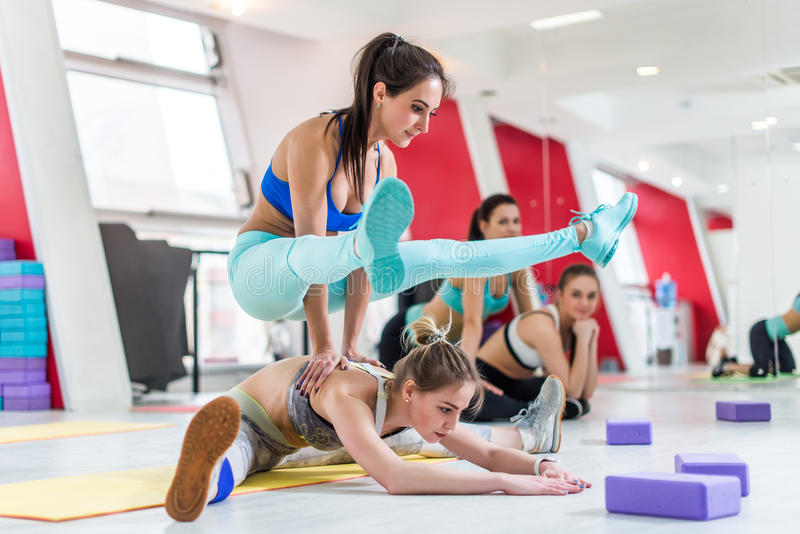 Woman sitting in wide-angle seated forward bend pose and another sportswoman doing firefly yoga pose standing on back of. Two girls doing stretching exercise stock image