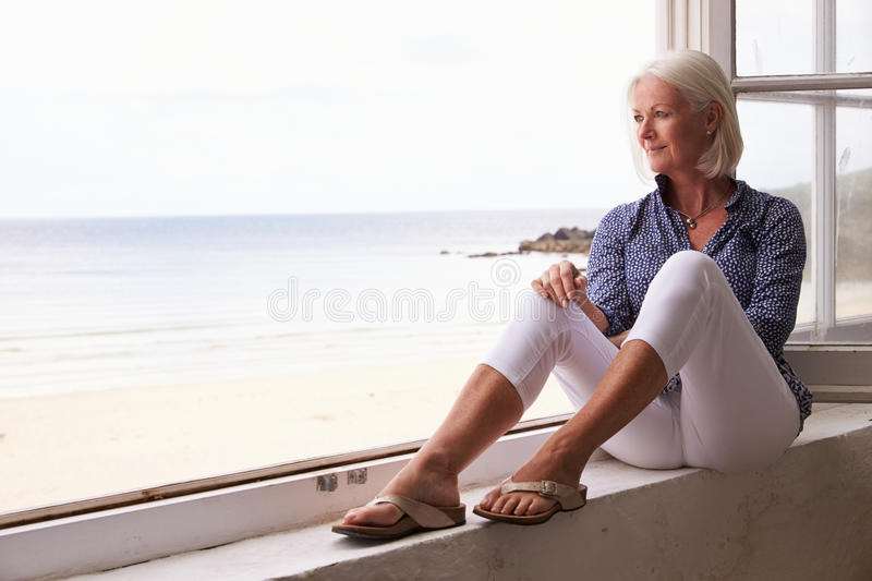 Woman Sitting At Window And Looking At Beautiful Beach View royalty free stock photos