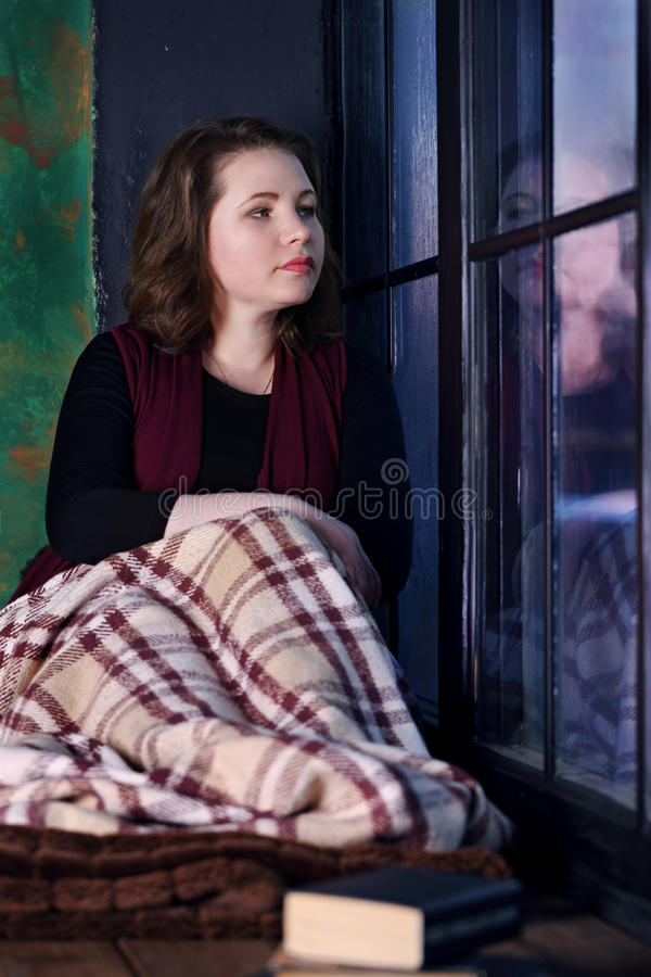 Woman sitting by the window royalty free stock image