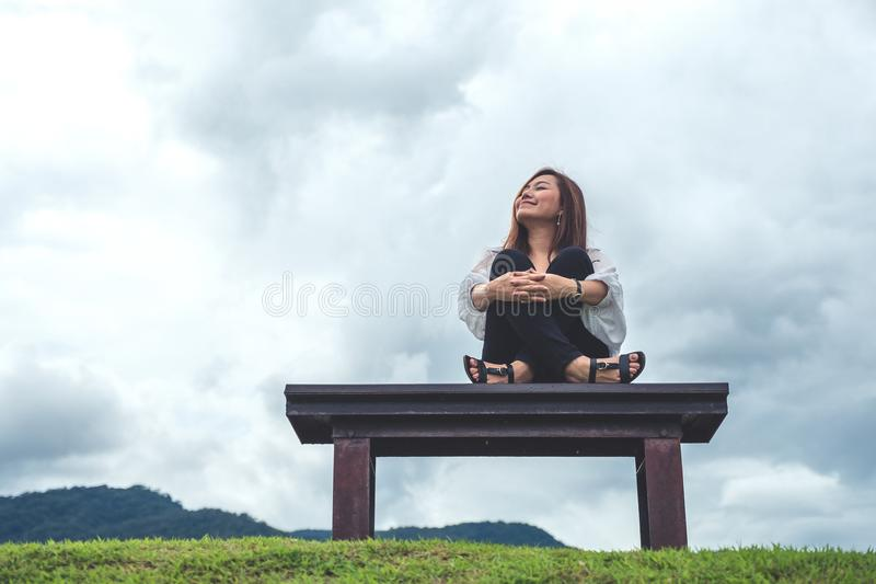 Woman sitting on a wooden bench in the park with blue sky background royalty free stock image