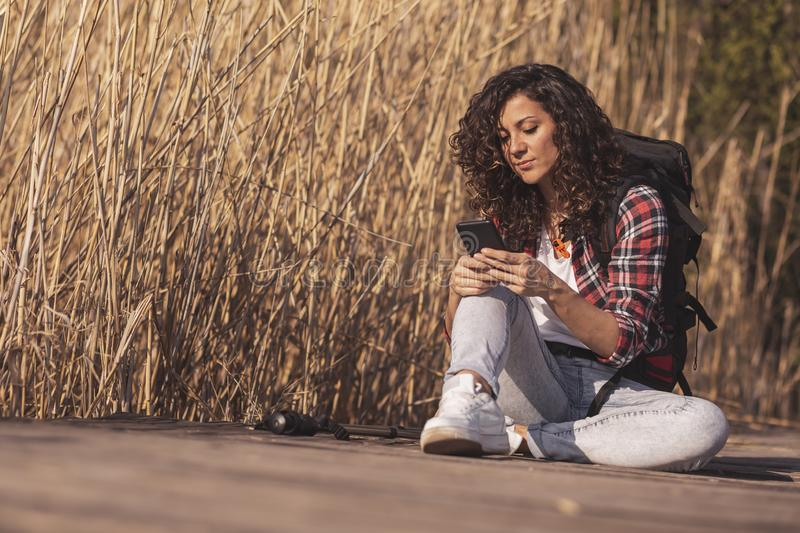 Woman typing a text message outdoors. Woman sitting on the wooden lake docks, enjoying an autumn day in nature, relaxing after hiking and typing a text message stock images