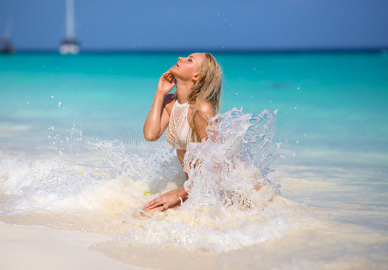 Woman sitting on the Zanzibar`s white sand beach. Beautiful blonde woman in the knitted white bikini sitting on the lonely evening beach with turquoise water and stock photography
