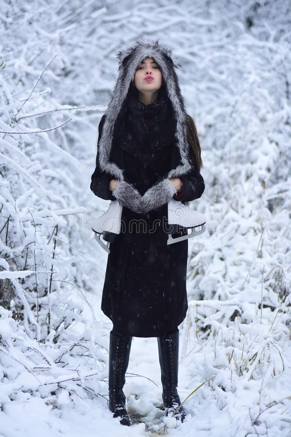 Woman with skating shoes in winter clothes in snowy forest. Girl with pair of figure skates at trees in snow. Sport, activity, health. Ice skating concept stock photography
