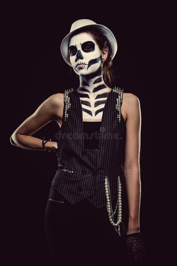 Woman with skeleton face art smoking. Woman with skeleton face art over black background stock photo