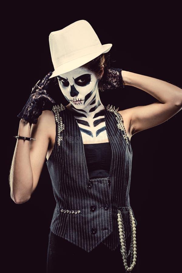 Woman with skeleton face art smoking. Woman with skeleton face art over black background stock photography